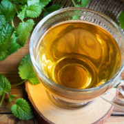 A cup of melissa (lemon balm) tea on a table with fresh melissa leaves